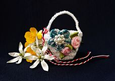 Handmade crocheted basket with spring flowers and red and white string, known as Martisor. Handmade crocheted basket with spring flowers and red and white stock image