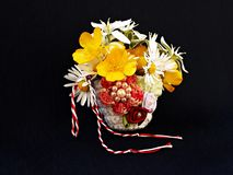 Handmade crocheted basket with spring flowers and red and white string, known as Martisor. Handmade crocheted basket with spring flowers and red and white stock photos