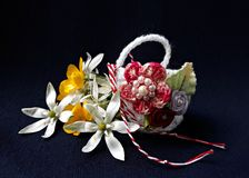 Handmade crocheted basket with spring flowers and red and white string, known as Martisor. Handmade crocheted basket with spring flowers and red and white royalty free stock photo