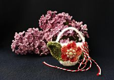 Handmade crocheted basket with spring flowers and red and white string, known as Martisor. Handmade crocheted basket with spring flowers and red and white royalty free stock images
