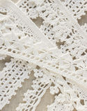 Handmade crocheted cotton organic lace ribbons on linen background. White original organic crochet frame, Knitted pattern backdrop Stock Images