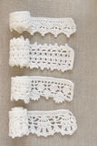 Handmade crocheted cotton organic lace ribbons on linen background. White original organic crochet frame, Knitted pattern backdrop Royalty Free Stock Photography
