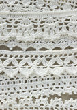 Handmade crocheted cotton organic lace ribbons on linen background. White original organic crochet frame, Knitted pattern backdrop Royalty Free Stock Photos