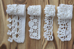 Handmade crocheted cotton organic lace ribbons on wooden background. White original crochet frame, Knitted pattern backdrop with h Royalty Free Stock Images