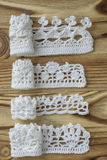 Handmade crocheted cotton organic lacen ribbons on wooden background. White original crochet frame, Knitted pattern backdrop with Stock Photography