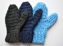 Handmade Crocheted Family of Mittens. A family of handmade, crocheted simple mittens on a white background stock images