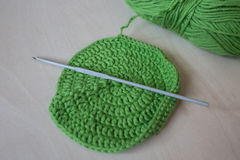 Handmade crocheted pot with green wool Stock Image