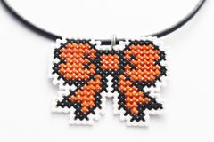 Handmade Cross Stitch Necklace Orange Ribbon. Embroidered on white plastic canvas royalty free stock photos