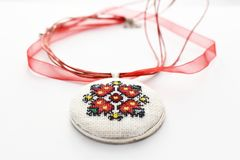 Handmade Cross Stitch Necklace Red Flower. Embroidered on white canvas, Micro embroidery royalty free stock image