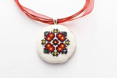 Handmade Cross Stitch Necklace Red Flower. Embroidered on white canvas, Micro embroidery royalty free stock photography