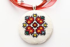 Handmade Cross Stitch Necklace Red Flower. Embroidered on white canvas, Micro embroidery royalty free stock images
