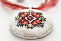 Handmade Cross Stitch Necklace Red Flower. Embroidered on white canvas, Micro embroidery royalty free stock photo