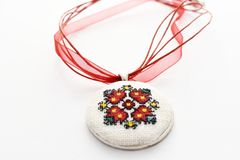 Handmade Cross Stitch Necklace Red Flower. Embroidered on white canvas, Micro embroidery stock photography