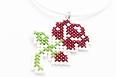 Handmade Cross Stitch Necklace Red Rose. Embroidered on white plastic canvas royalty free stock photography