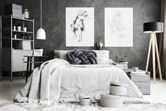 Handmade cushion on bed. Handmade knot cushion placed on the bed with grey bedding in spacious bedroom interior with posters and rack in the background stock photo