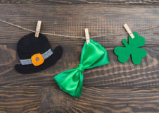 Handmade decoration St. Patricks Day hat, bow, clover leaf. Handmade decoration St. Patrick`s Day hat, bow, clover leaf hanging from rope on clothespin. Brown Royalty Free Stock Images