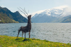 The handmade deer on a fjords shore. The picture of the deer made from a twigs on the backgound of the fjords mountains royalty free stock photos