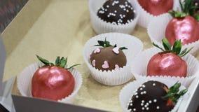 Handmade dojrzałe truskawki zakrywać z zmrokiem, mlekiem i menchii czekoladą, są w pudełku Zoomu ruch zbiory