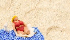 Handmade doll in beach scene. Tourist woman with fat body in red bikini. Stock Photography