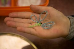 Dragonfly made of beads on child`s hand Royalty Free Stock Photo