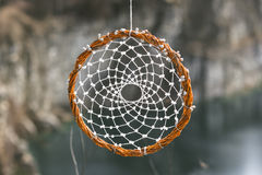 Handmade dream catcher on background of rocks and lake Royalty Free Stock Photo