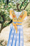 Handmade dress. Blue yellow handmade dress hanging on tree Stock Photo