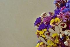 Handmade drewniany słowo «miłość «z pięknym lato bukietem ogrodowi kwiaty - limonium na beżowym koloru tle zdjęcia royalty free