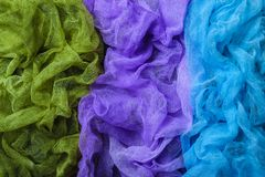 Dyed gauze fabric. Handmade dyed textured gauze fabric background. Blue, purple and green colors. Top view stock image