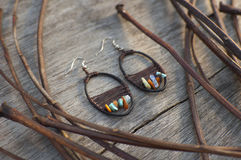 Handmade earring in boho style made with eco materials lying at. Wooden background with natural tree twigs royalty free stock image