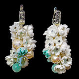 Handmade earrings. Close-up view to handmade earrings with a freshwater pearls, agate, nacre and small flowers from foamiran (artificial suede), similar to the Stock Photos