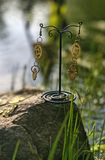 Handmade. Earrings with gears on the stone on sunny day. Handmade. Earrings with gears on the stone on summer sunny day Stock Photography