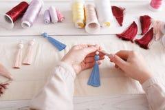 Handmade earrings making, home workshop. Woman artisan create tassel jewelry, top view. Art, hobby, handicraft concept Stock Photo