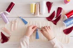 Handmade earrings making, home workshop. Woman artisan create tassel jewelry, top view. Art, hobby, handicraft concept Stock Image