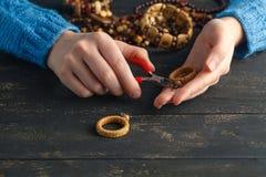 Handmade earrings making, home workshop. Woman artisan create tassel jewelry. Art, hobby, handicraft concept Royalty Free Stock Photo