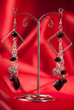 Handmade earrings over red Royalty Free Stock Photos