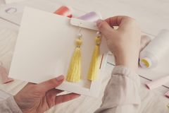 Handmade earrings packing, home workshop. Woman artisan put tassel jewelryinto original boxes, top view, filtered image. Art, hobby, handicraft concept Royalty Free Stock Images
