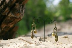 Handmade. Earrings on the stand with buddhas on sand. On sunny day Royalty Free Stock Images