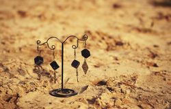 Handmade. Earrings on the stand on sand. On sunny day Stock Photo
