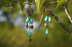 Handmade. Earrings with stones and golden hearts on the tree branch. On sunny day Stock Photography