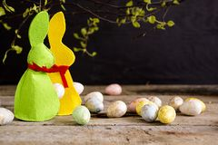 Handmade easter bunnies and eggs on wooden table. Branches of young tree on dark background. Copy space Stock Photo
