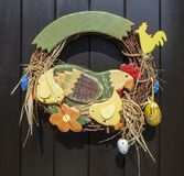Handmade Easter decoration with hen and chicks in colored wood. Brown background royalty free stock image