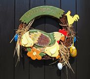 Handmade Easter decoration with hen and chicks in colored wood. Brown background. german language welcome stock photos