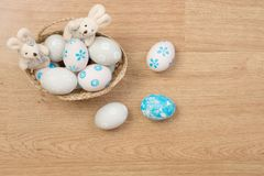 Handmade easter eggs and rabbit doll in a basket isolated on woo. Den background Royalty Free Stock Photography
