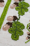 Handmade embroidery by cross stitch. Handmade Embroidery by Cross Stitch in the View of Acorns. Texture of Beige Natural Linen Fabric with Embroidery for Stock Image