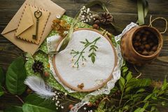 Handmade embroidery, green leaves, nuts, white flowers. Wooden embroidery frame royalty free stock photo