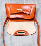 Empty orange colored leather bag on gray table royalty free stock photos