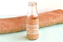 Handmade empty vase, burlap, wooden background. Home made vase. Simple and cheap DIY recycled material Royalty Free Stock Images