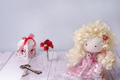Handmade fabric doll girl on a white wooden table copyspace with fairy key, paper rose and gift box stock images