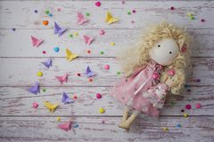 Handmade fabric doll near colorful beads, paper butterflies stock images