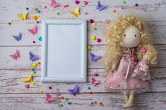 Handmade fabric doll with colorful beads, paper butterflies and white photo frame royalty free stock photos